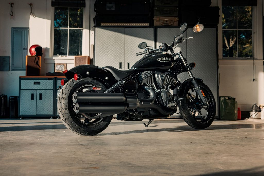 The rear 3/4 view of a black 2022 Indian Chief in a sunlit garage