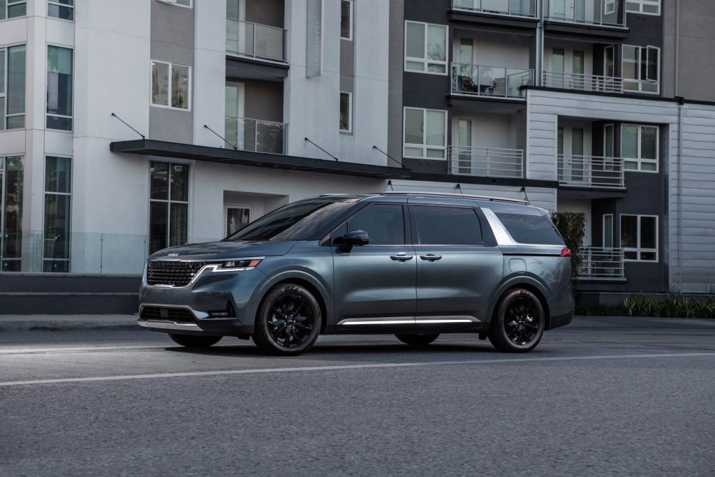 A turquoise 2022 Kia Carnival driving down a city road