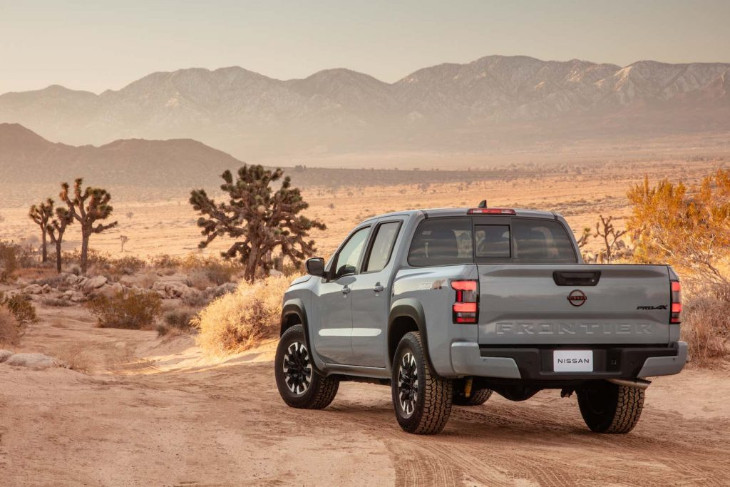a rear quarter view of the 2022 nissan frontier driving off into the dessert.
