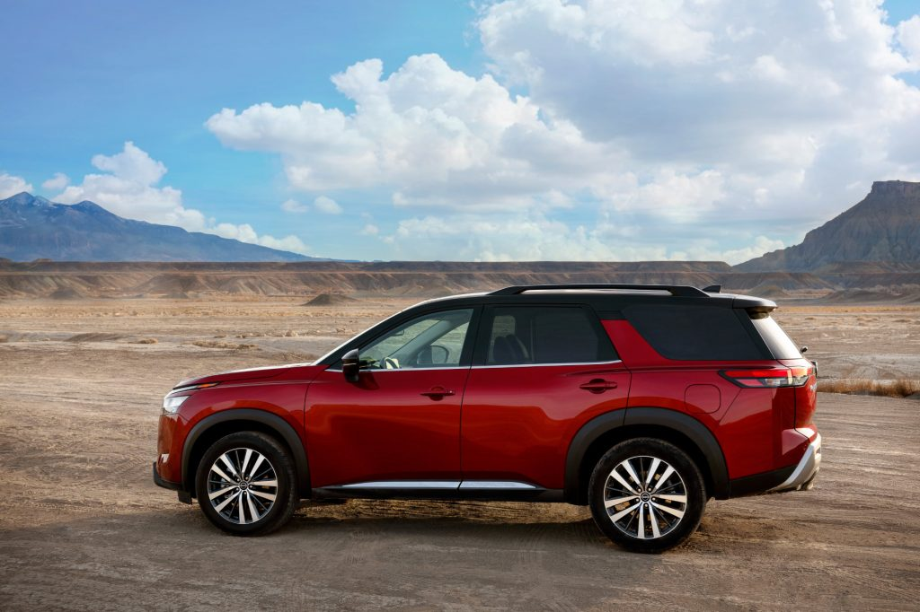 A red 2022 Nissan Pathfinder parked on a dirt road