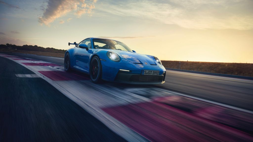 A blue 2022 Porsche 911 GT3 drives around a racetrack at sunset