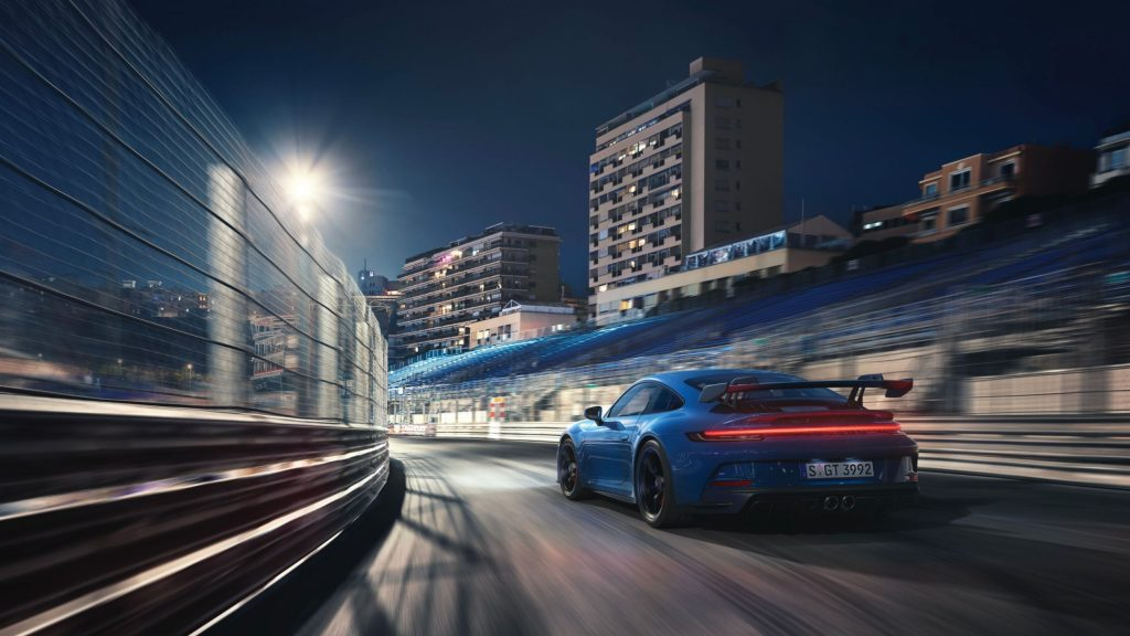 The rear 3/4 view of a blue 2022 Porsche 911 GT3 on a racetrack at night