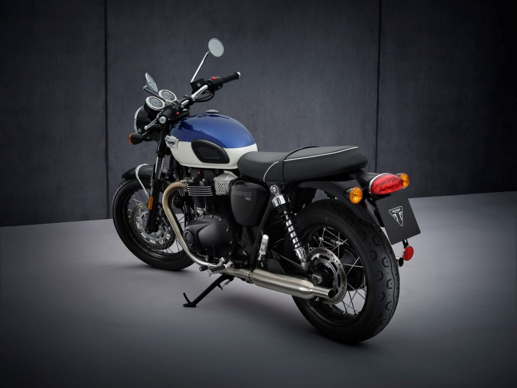 The rear 3/4 view of a blue-and-white 2022 Triumph Bonneville T100 in front of a gray background