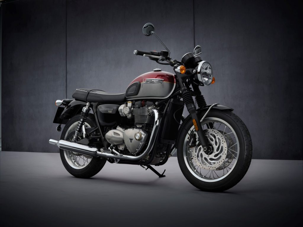 A red-and-silver 2022 Triumph Bonneville T120 in front of a gray background