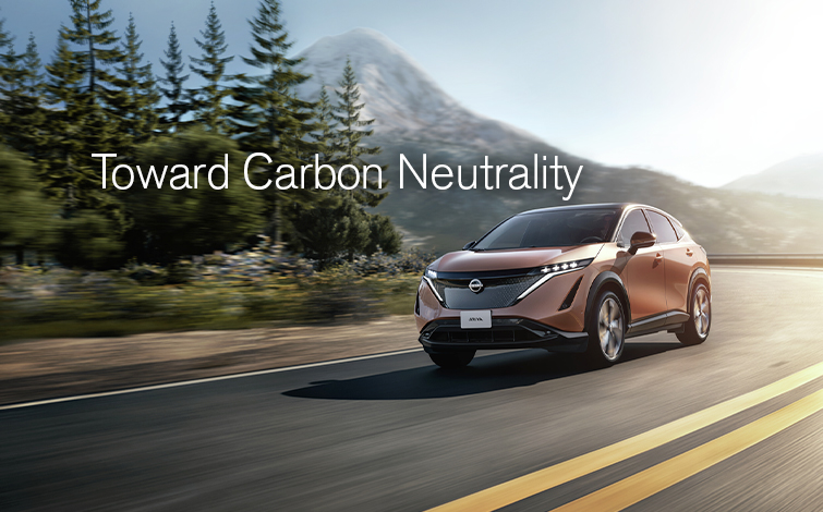 """A red Nissan SUV driving down a road with a text block above it that reads """"toward carbon neutrality"""""""