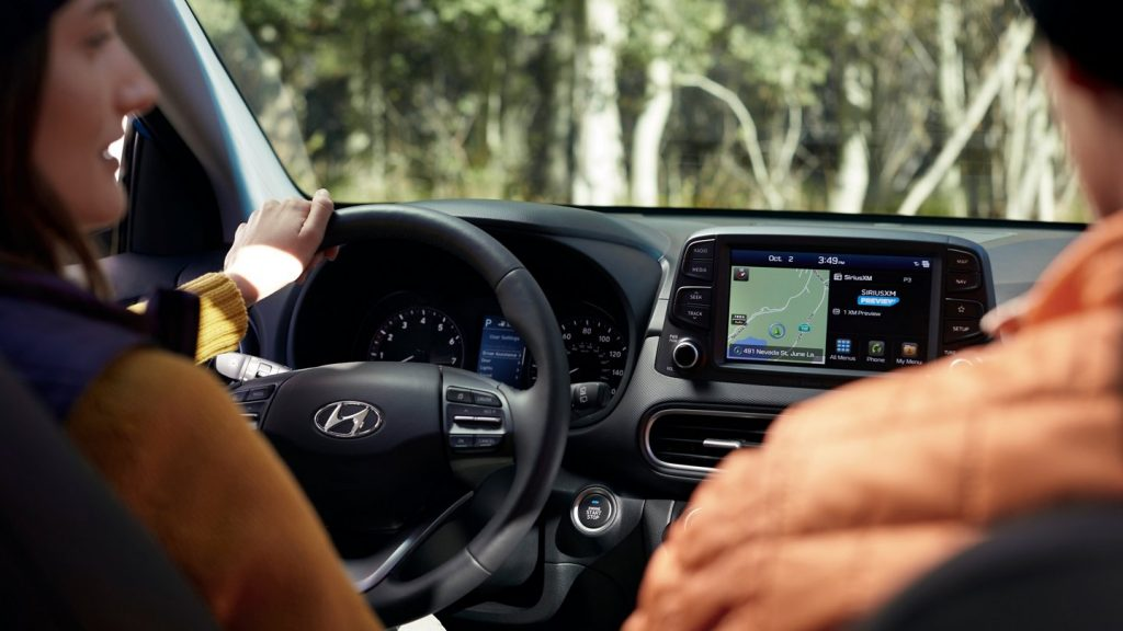 a picture of a woman driving the 2021 hyundai kona from the view of a rear seat passenger