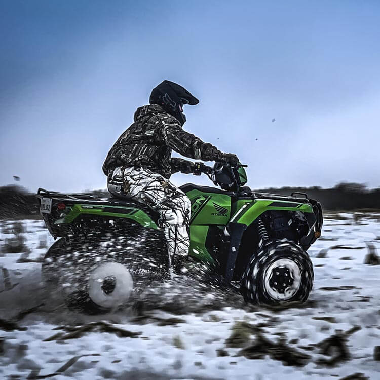 a bright green honda fourtrax foreman rubicon ATV in the snow