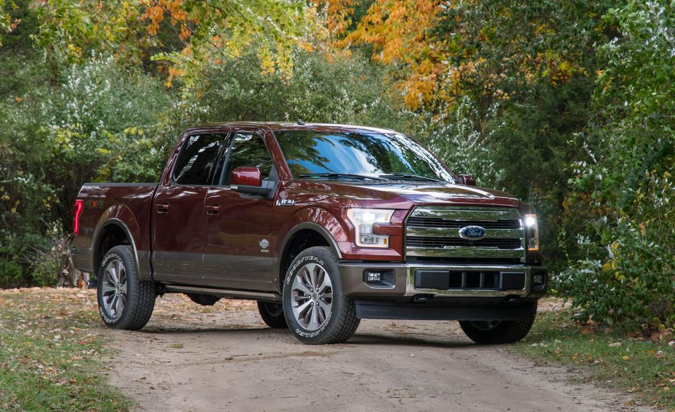 a dark red 2017 King Ranch Ford F-150 pickup truck parked on a dirt road in the forest