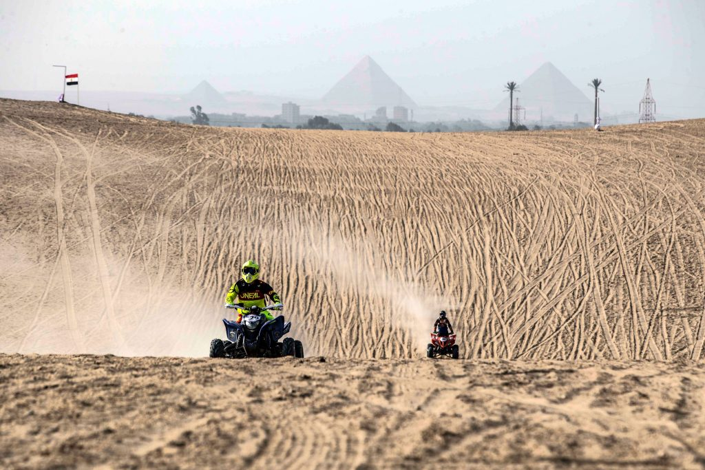 two riders going head to head in an ATV race in the sahara desert with egyptian pyramids in the background