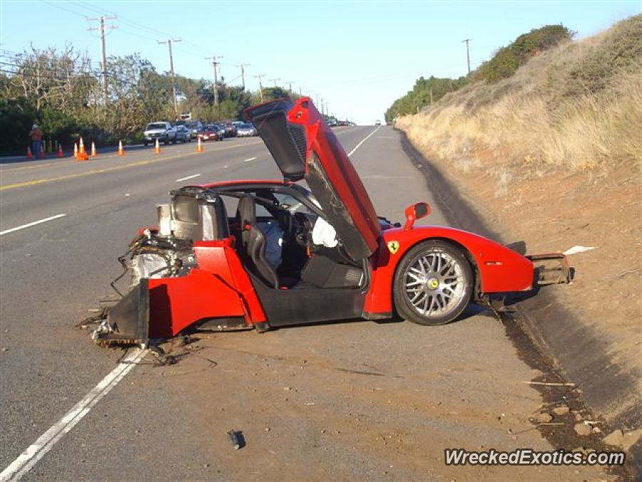 An image of a crashed Ferrari Enzo on the side of the road.