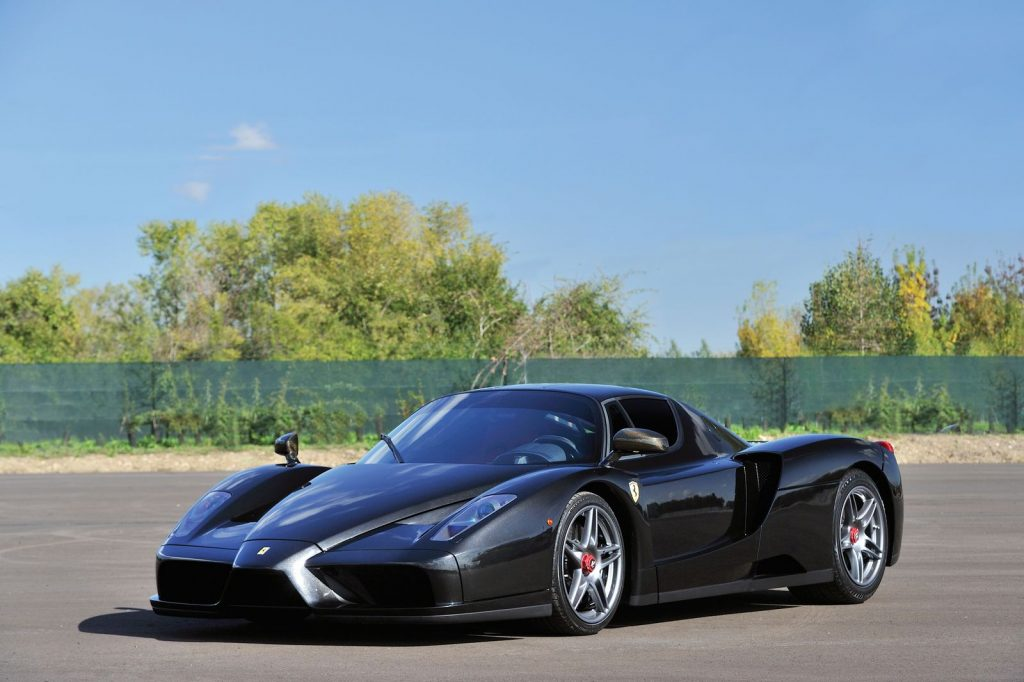An image of a black Ferrari Enzo parked outside.