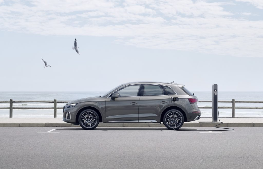 A side image of a 2021 Audi Q5 55 TFSI e quattro  in Daytona grey plugged into a hybrid charging station along the water