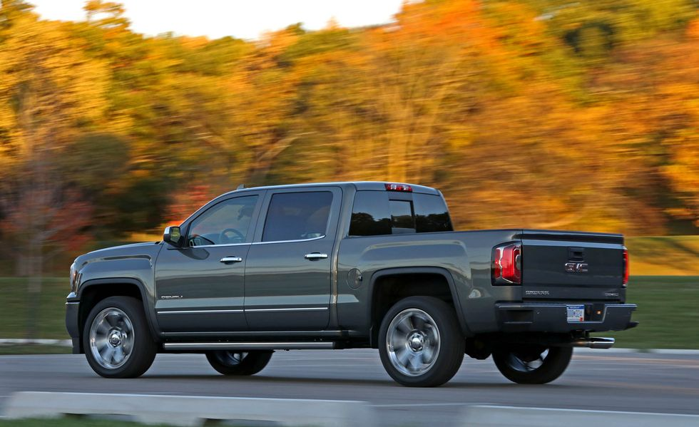 a side view of a gray 2017 GMC Sierra at speed on a road with autumn trees in the background