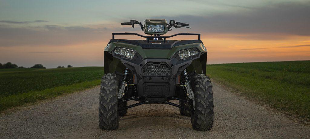a green polaris sportsman ATV on a ranch road at dawn