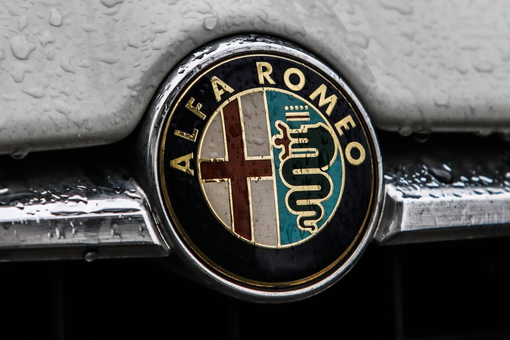 A close-up view of an Alfa Romeo badge on the front of a car