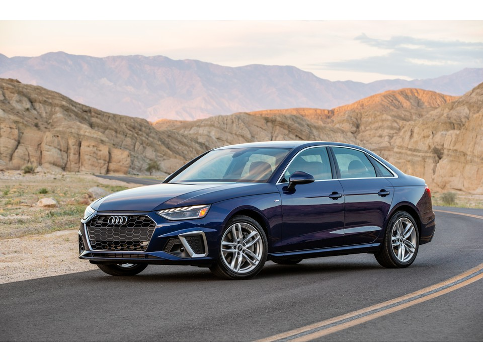a 2021 Audi A4 parked on a desert road with a sandy mountainscape in the background