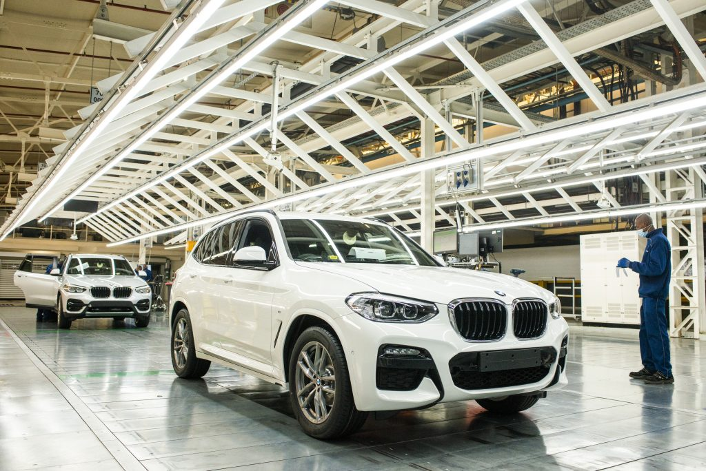 A worker wearing a protective face mask checks the bodywork of an BMW X3 sport utility vehicle (SUV) in a light tunnel at the BMW South Africa Pty Ltd. Rosslyn plant