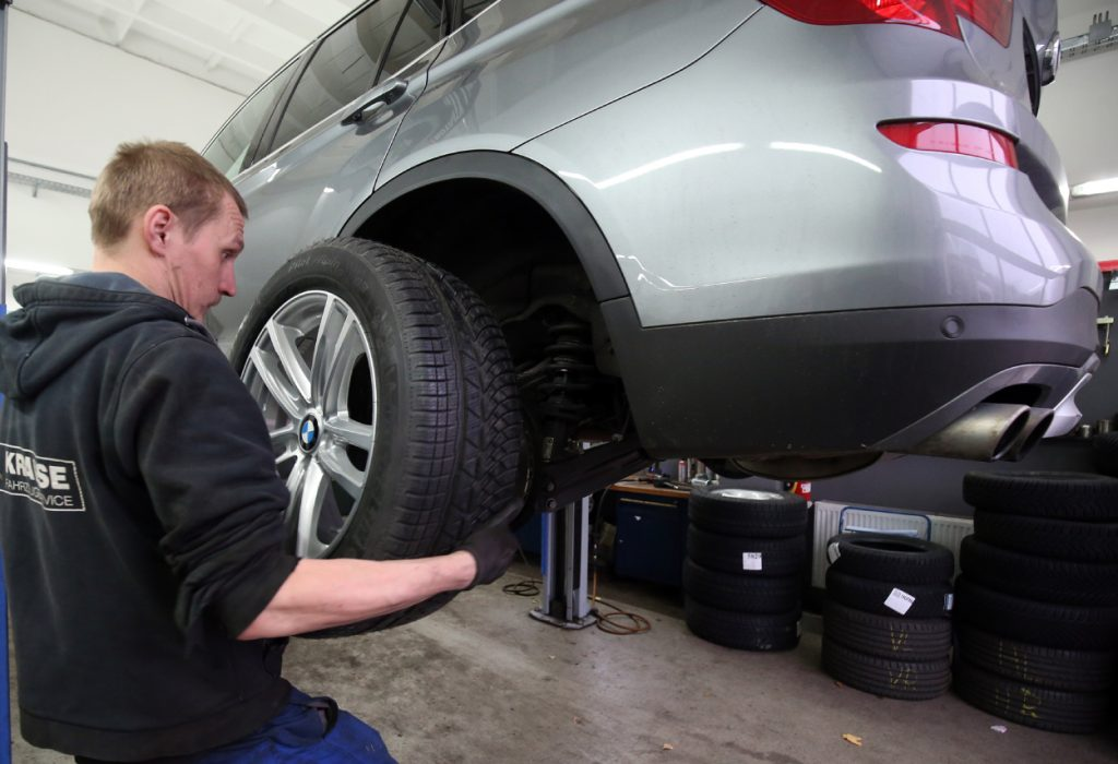 An auto mechanic changes the tires on a car