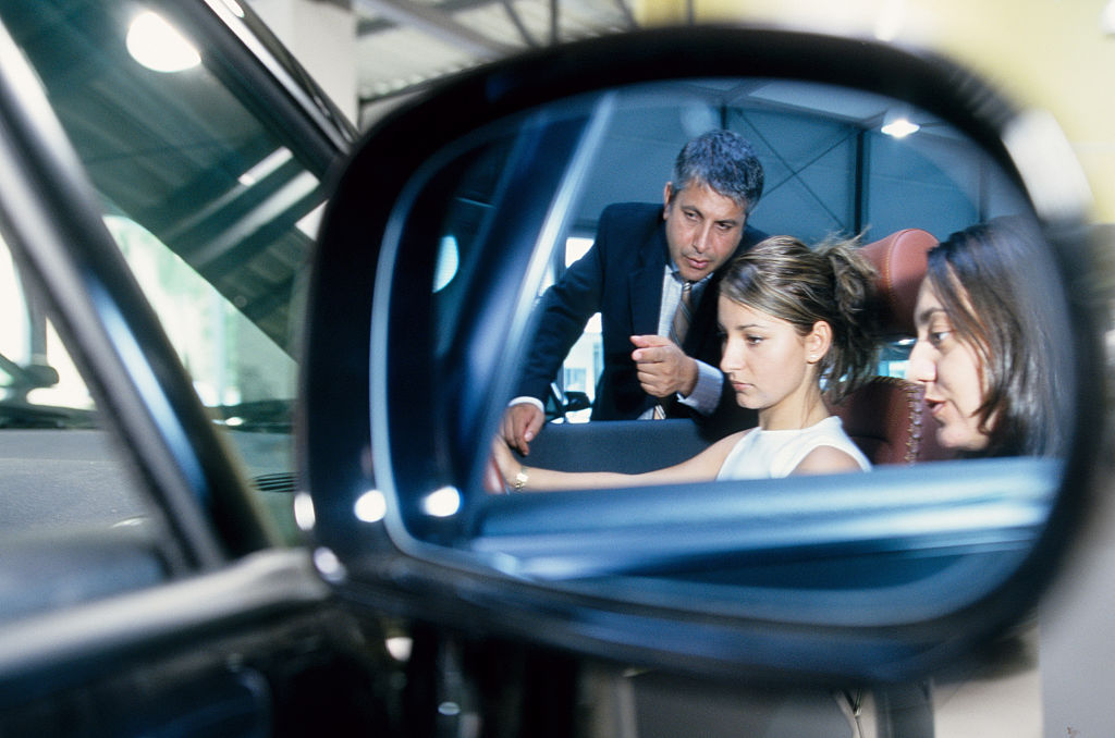 mirror reflection of woman being sold car by salesman