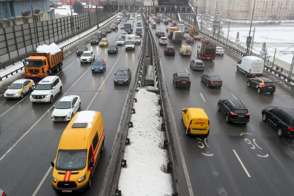 Cars and other vehicles drive on a snowy divided highway