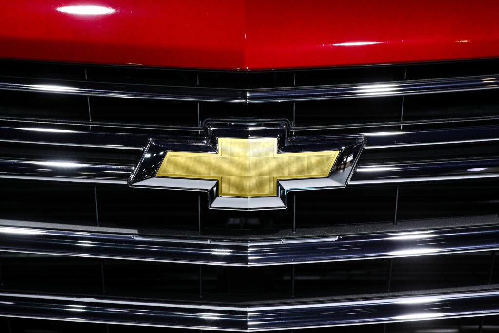A close-up of Chevy's bow-tie logo on the grille of a car