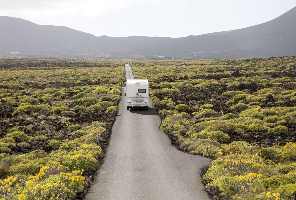 An RV driving down an empty road.