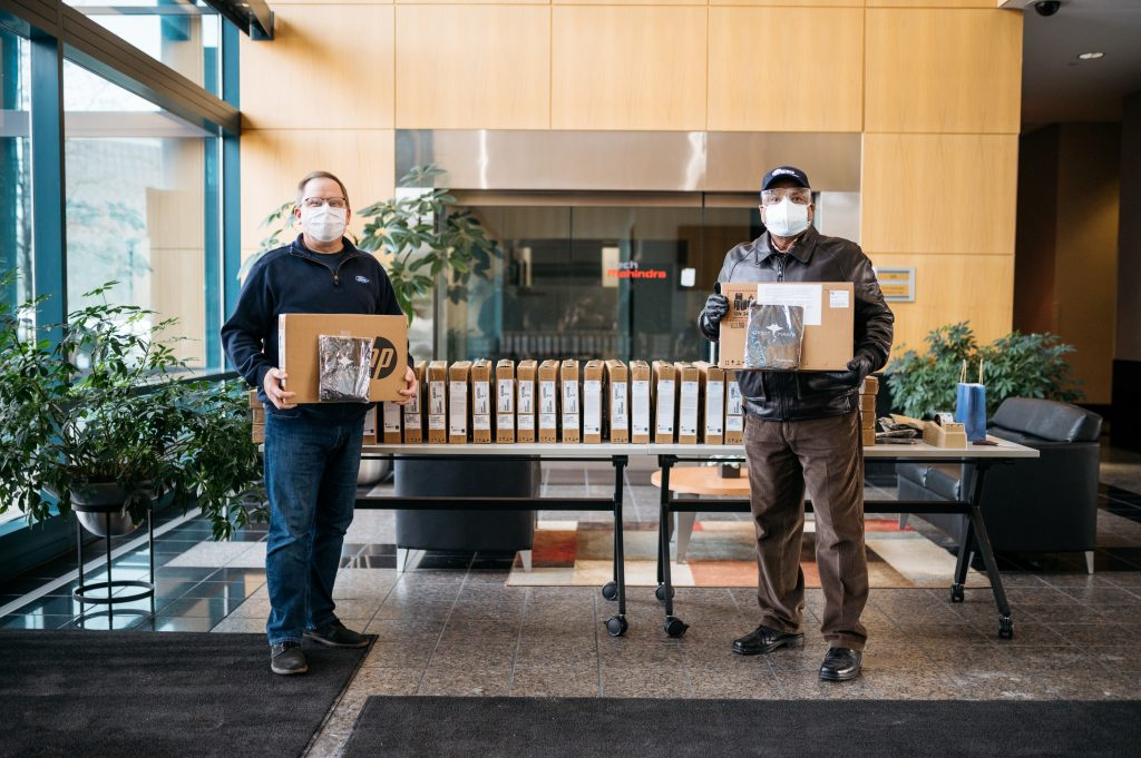 Two men stand holding laptops to be donated to the Girls in Engineering Academy