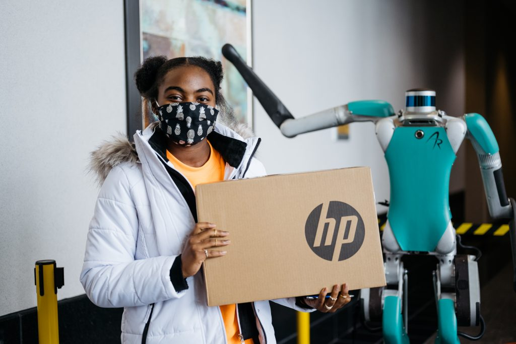 A young girl at the Girls in Engineering Academy holds a laptop box donated by Ford