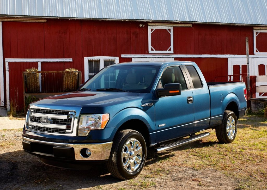 a blue 2013 Ford F-150 poses in front of a barn