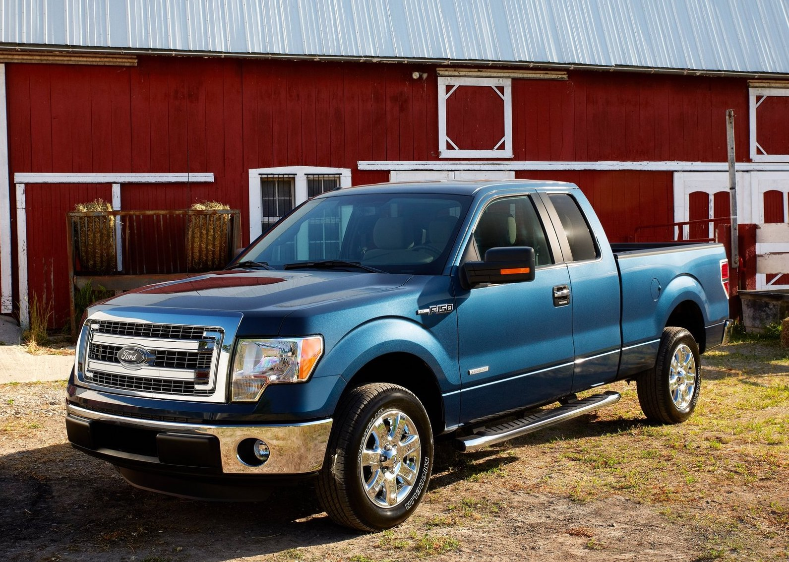 a blue ford f-150 from the 2013 model year barked in front of a scenic red barn