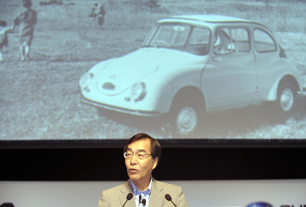 Fuji Heavy Industries president and CEO Ikuo Mori delivers a speech in front of an image of the Subaru 360