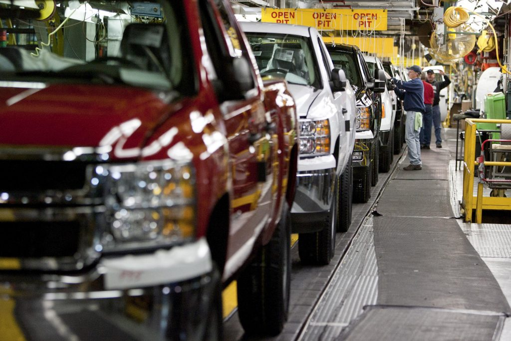 Chevy Silverado and GMC Sierra trucks being inspected on the assembly line