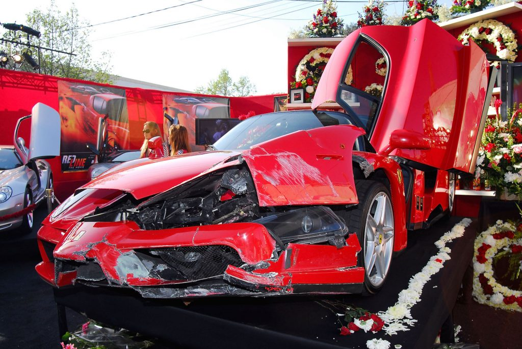An image of a crashed Ferrari Enzo parked up on display.