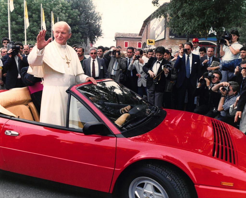 An image of John Paul II riding on a convertible Ferrari.