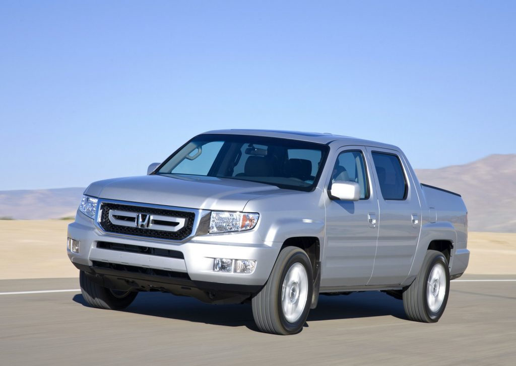 a silver 2009 honda ridgeline pickup truck driving in the sand