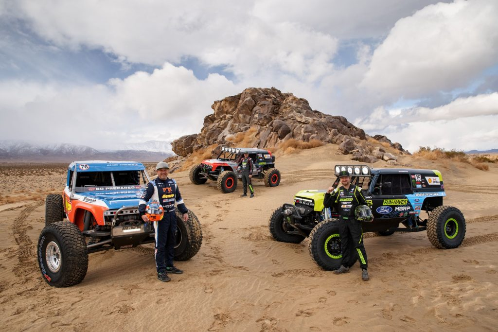 (Clockwise from left) Jason Scherer, Loren Hauley, and Vaughn Gittin, Jr., with their 2021 Ford Bronco 4400 King of the Hammers racers by a desert rock formation