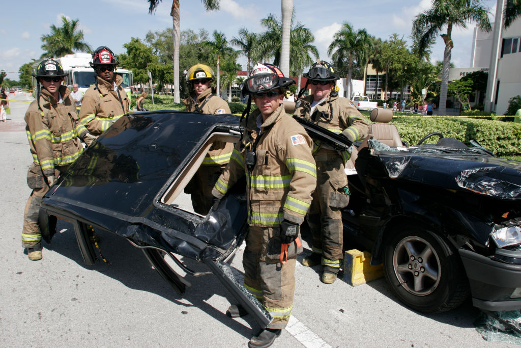 Jaws of life and car top with firefighters posing