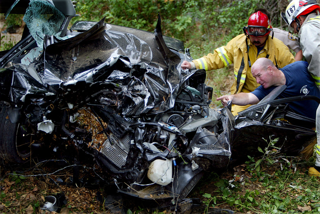 Mangled remains of car with firemen looking on