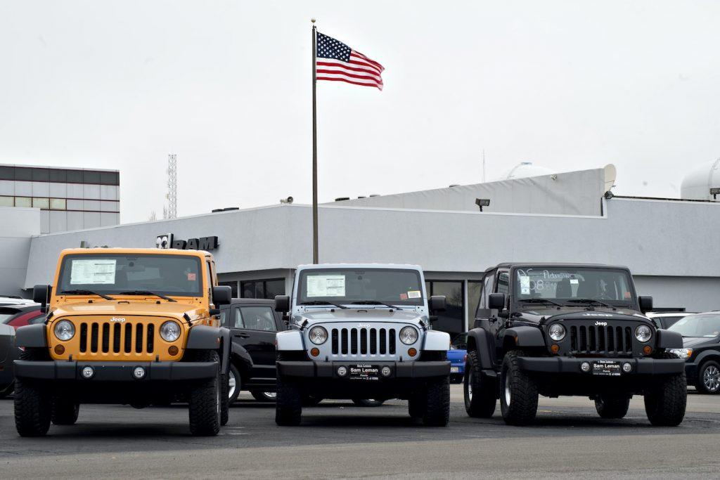 A U.S. flag flies over a car dealership.