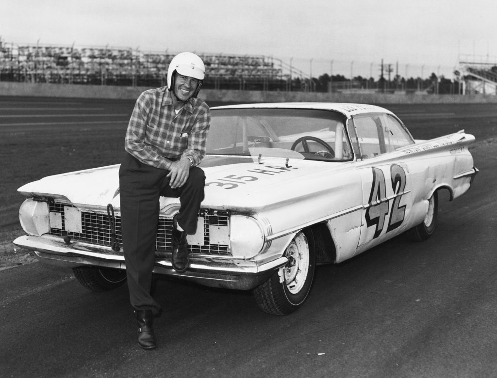 Lee Petty sitting on the hood of his No. 42 1959 Oldsmobile Super 88 before the start of the first Daytona 500