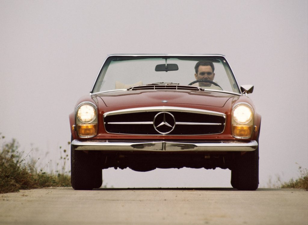 An image of a Mercedes-Benz 230 SL driving down the road.