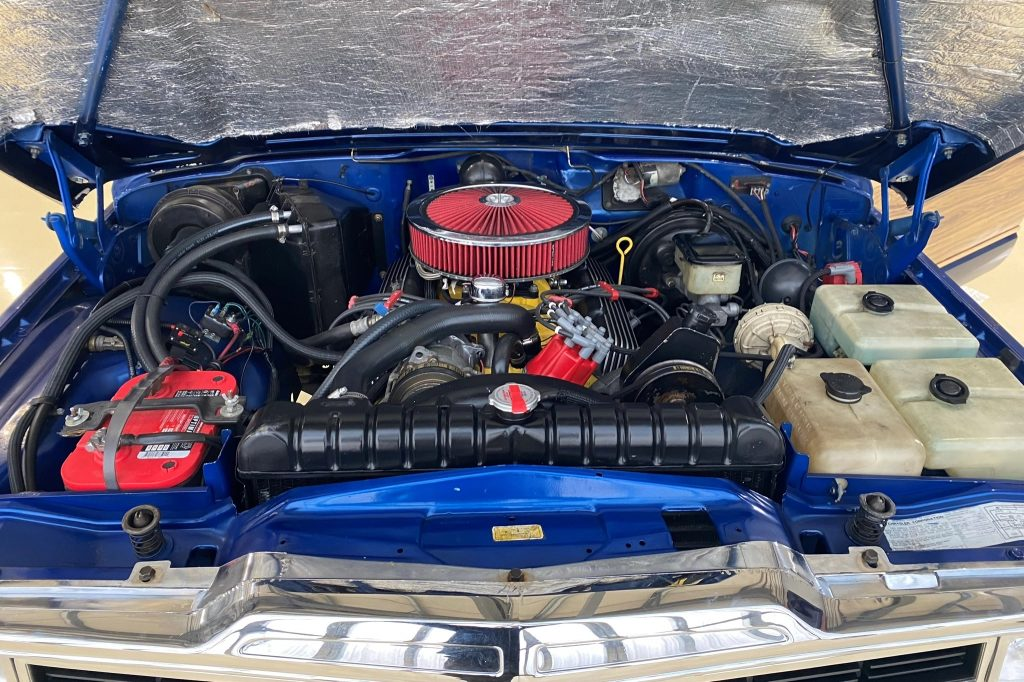 The engine bay of a modified blue 1991 Jeep Grand Wagoneer