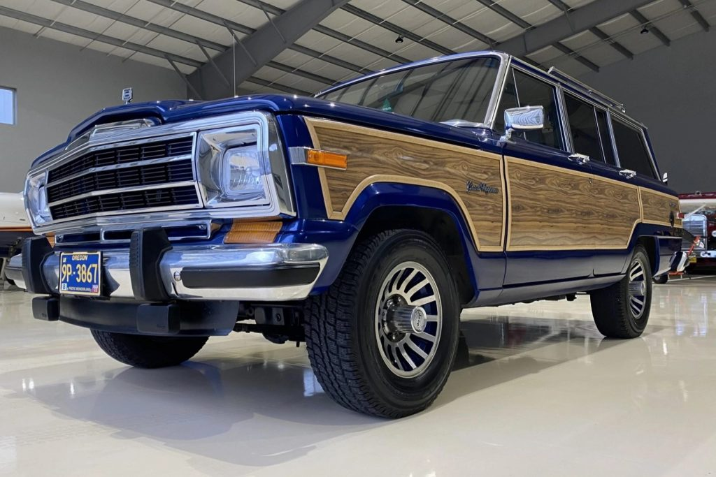 A low-angle front 3/4 view of a modified blue 1991 Jeep Grand Wagoneer in a hanger