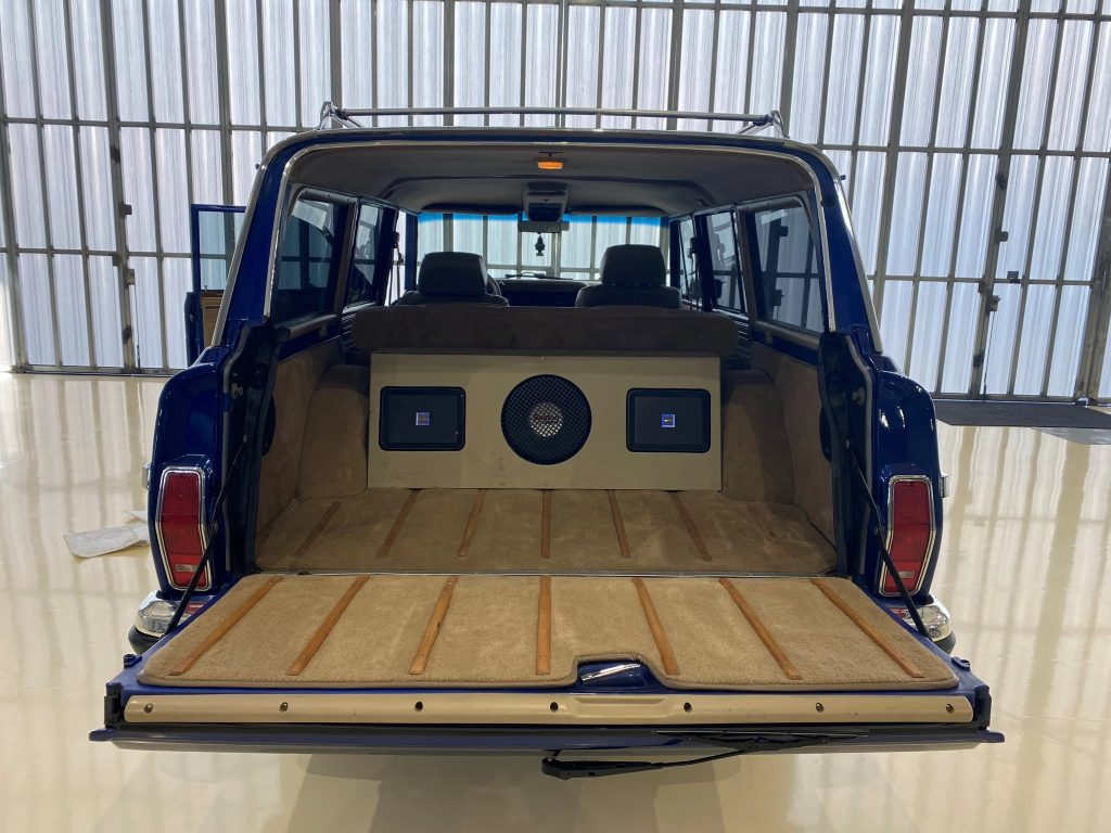 The view of a modified 1991 Jeep Grand Wagoneer's interior from the open rear tailgate