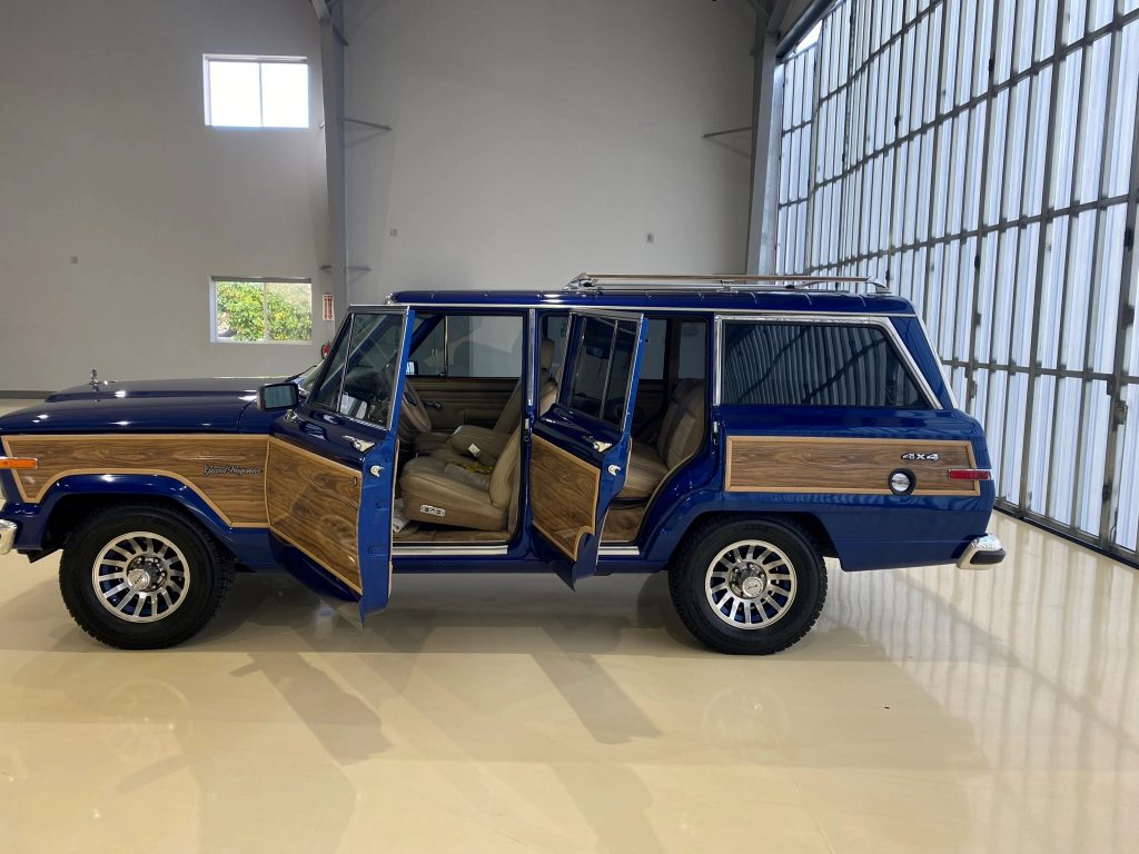 The side view of a modified blue 1991 Jeep Grand Wagoneer with its doors open