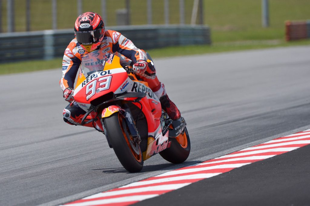 MotoGP rider Marc Marquez starts to countersteer his orange-and-red Repsol Honda motorcycle into a corner