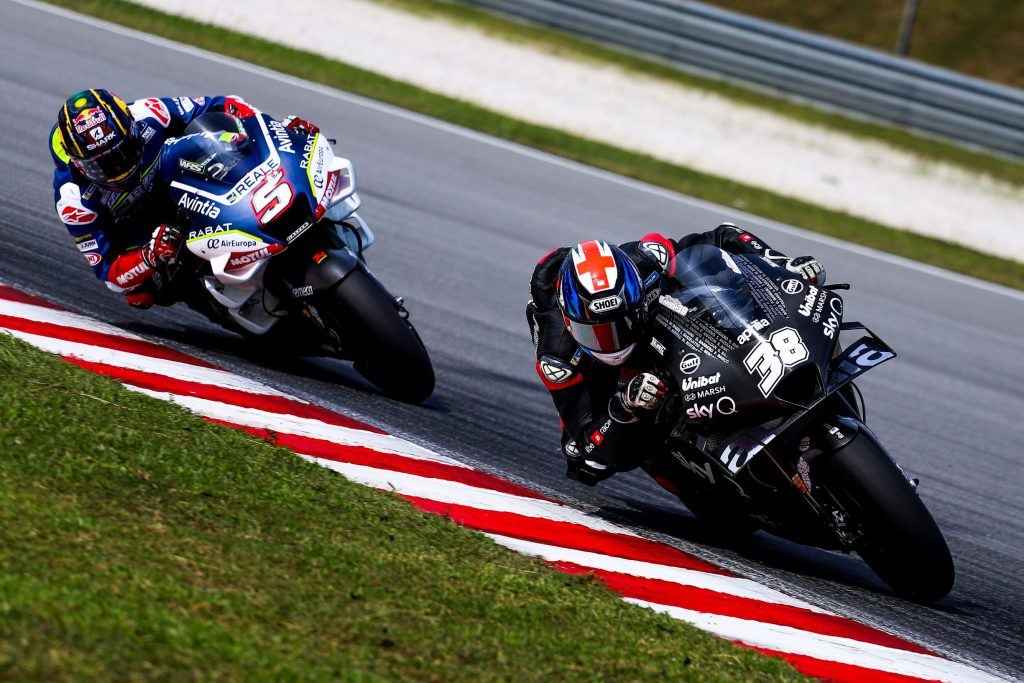 MotoGP riders Bradley Smith on a black-and-white bike and Johann Zarco on a white-and-blue bike countersteer their motorcycles around a corner