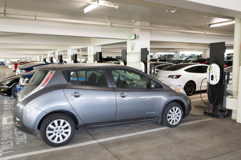 A Nissan Leaf electric car plugged into a charger
