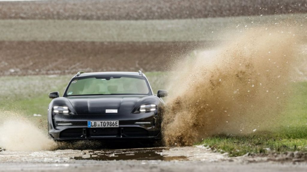 The front view of the black Porsche Taycan Cross Turismo prototype driving through a muddy and watery field