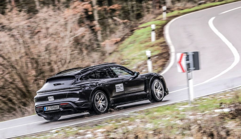 The rear 3/4 view of the black Porsche Taycan Cross Turismo prototype driving up a curving forested backroad